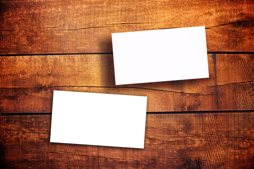 Blank Horizontal Business Cards as copy space for your design on Wooden Table
